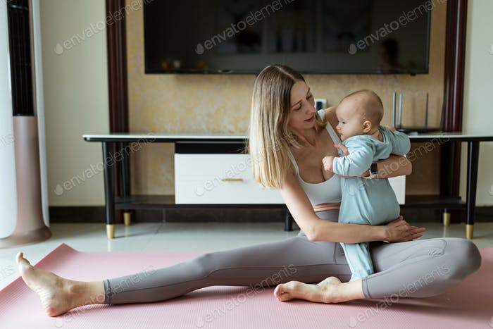Young mother in sport clothing exercising at home with baby. Online training during coronavirus