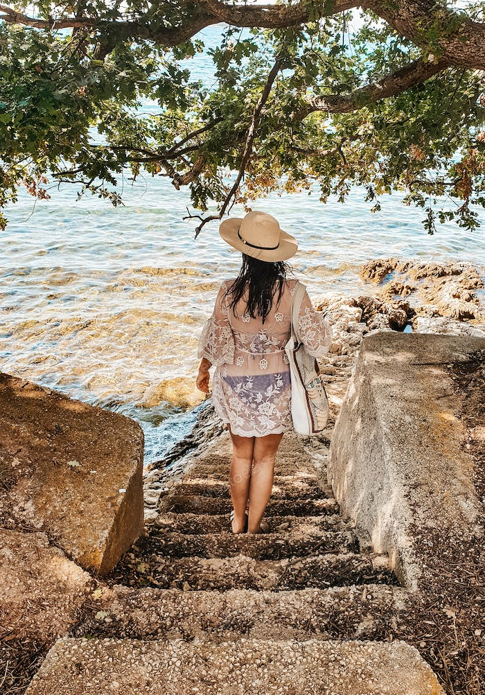 Woman from behind walking down stairs to beach. Summer, lifestyle, summer style, hat.