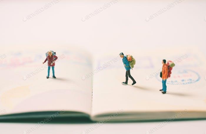 Mochila de personas en miniatura en la página del pasaporte con sellos de inmigración, viajes y concepto de vacaciones