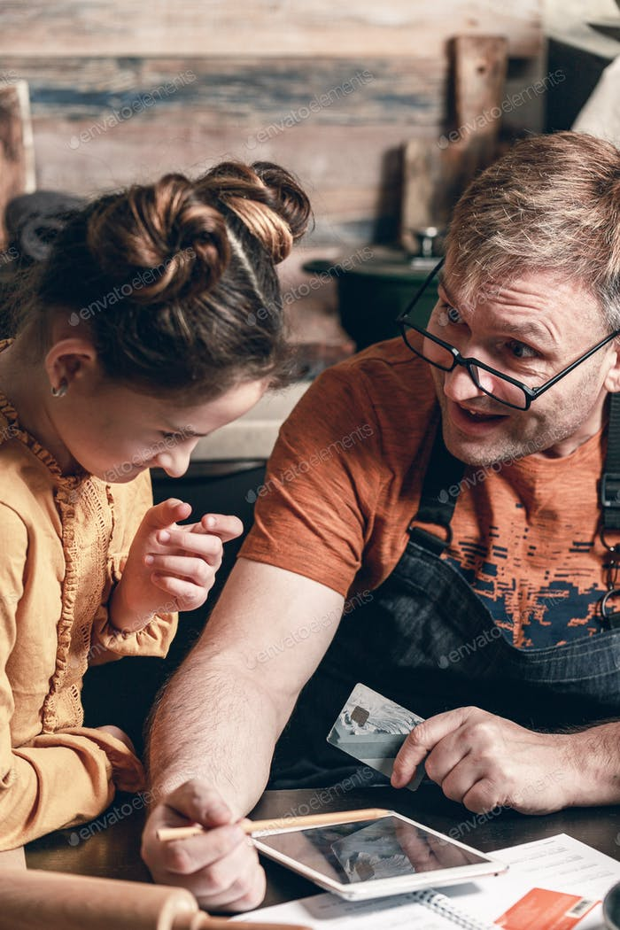 Отец с дочерью с кредитной картой покупки онлайн в продуктовом магазине. Фотография в стиле жизни