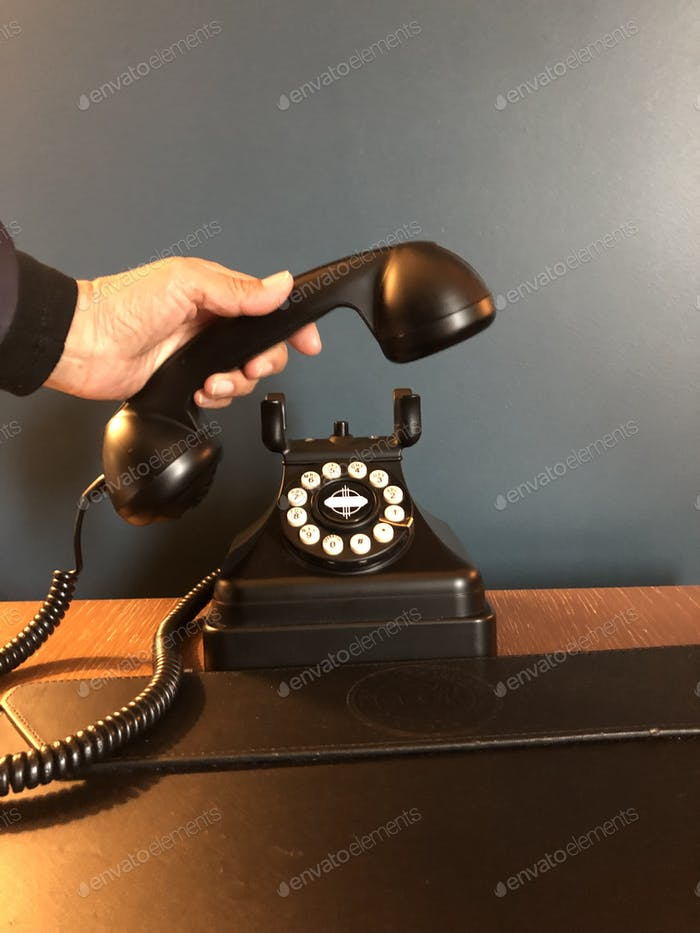 Antique vintage black rotary telephone on a desk.