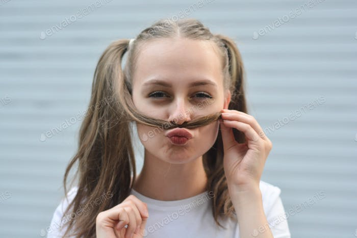 Having fun teen age girl - smiling and making mustache with strand of hair