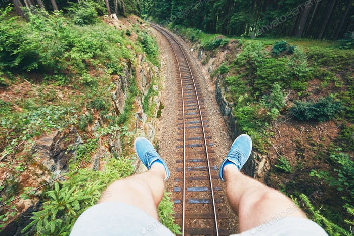 Man sitting above railroad track in the middle of the deep forest. Ore Mountains, Czech Republic