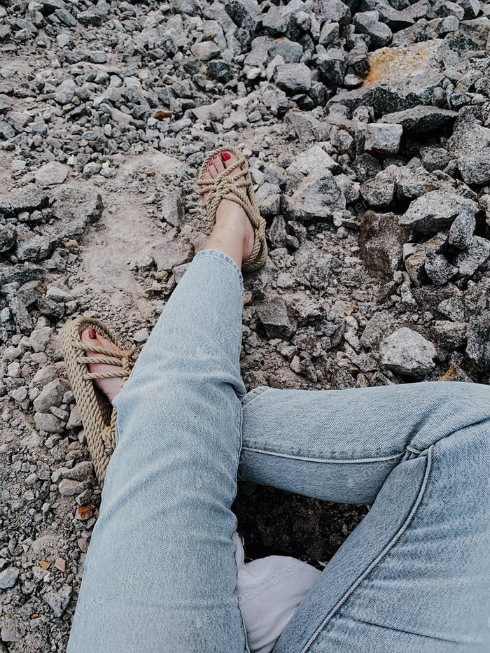 Legs in rope sandals on stone beach