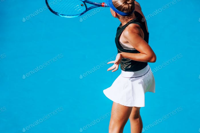 playing tennis, young athlete, competitive sport, action shot, minimal portrait on blue background