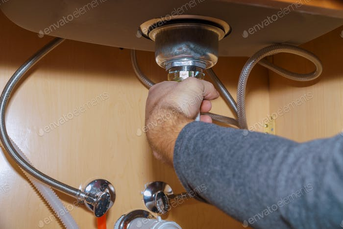 Plumber Install a Sink In kitchen of plumber repairing drain