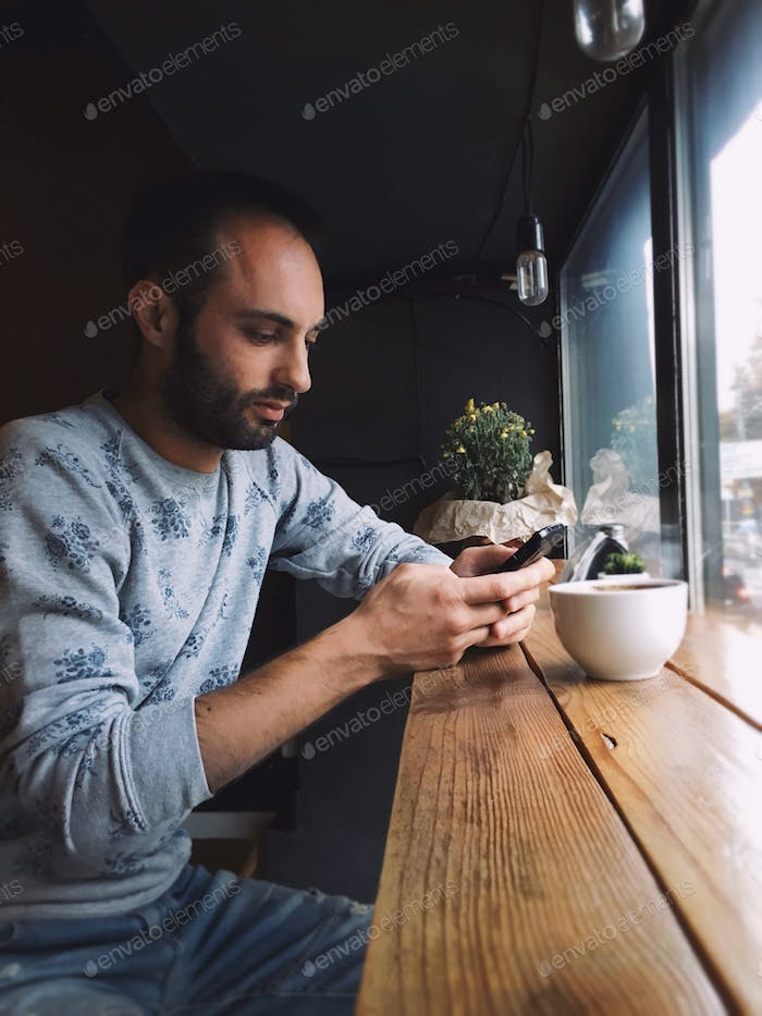 Bearded man using mobile at the cafe