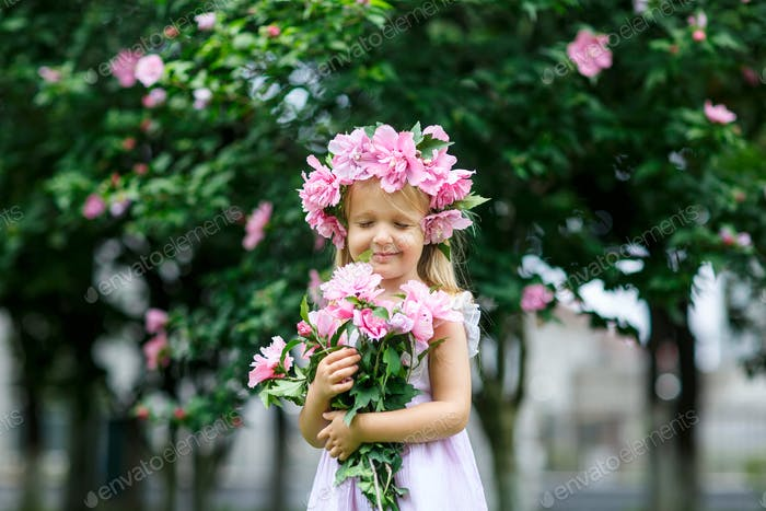 Happy little girl with blonde hair and flower wreath on her head holding hands bouquet of pink