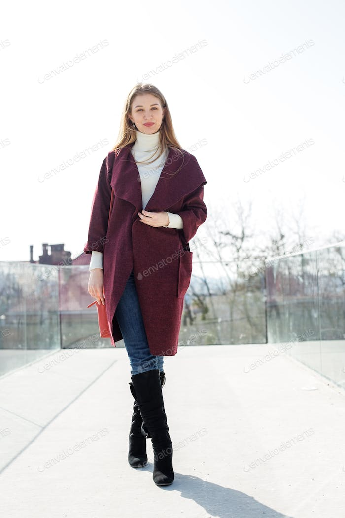 A woman in a purple coat with three-quarter sleeves in high boots on a city street