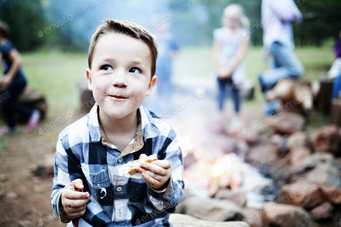 Little boy eating s'mores by a campfire