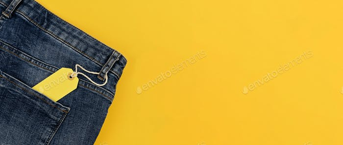 Long banner discount tag with blue jeans isolated on vivid yellow background, copy space, flat lay