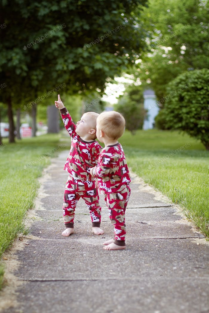 Twins outside pointing at airplanes