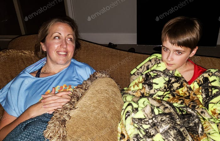 Mom and son watching television in basement bedroom.