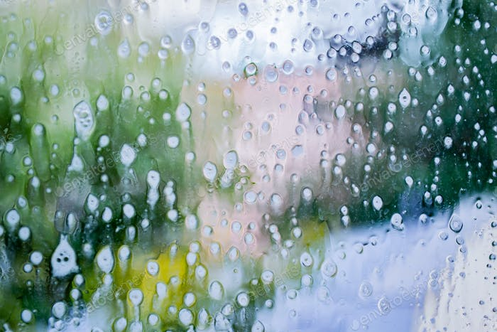 Glas in seifigen Streifen, Flecken und Wassertropfen. Außerhalb des Fensters verschwommene Straße, Häuser, Grün