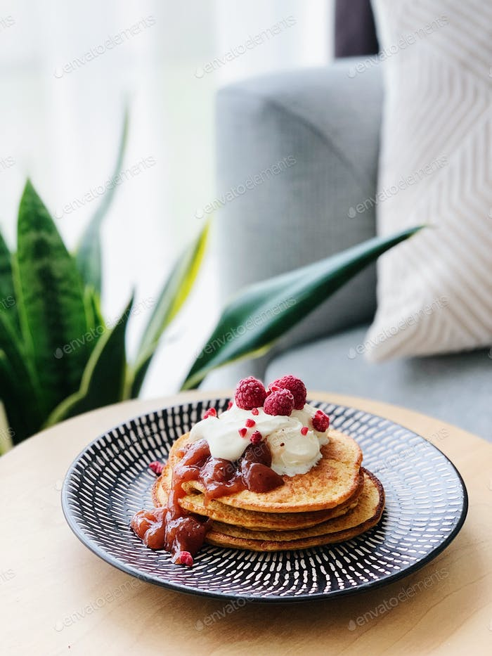 Beautifully styled pancakes with fresh berries and cream