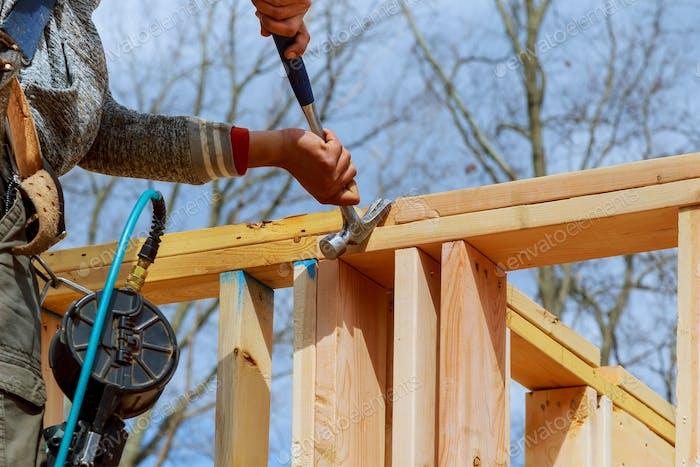 Authentischer Bauarbeiter, der Bauunternehmer mit Nagelpistole einrahmt