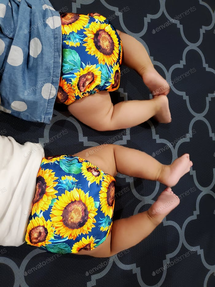 Umweltfreundliche bunte Stoffwindeln sind auf zwei Babys gesehen, die auf dem Bauch liegen