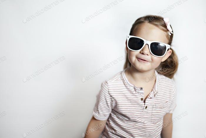 Mädchen mit weißer Sonnenbrille lächelnd