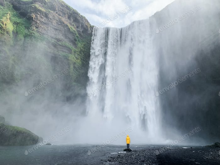 Human from behind the huge Iceland waterfall in yellow raincoat