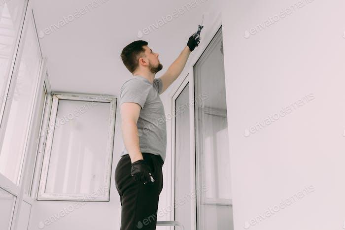 Trabajador manual de 30 años con herramientas de enlucido de pared dentro de una casa