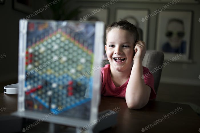 Boy playing a game of strategy battleship