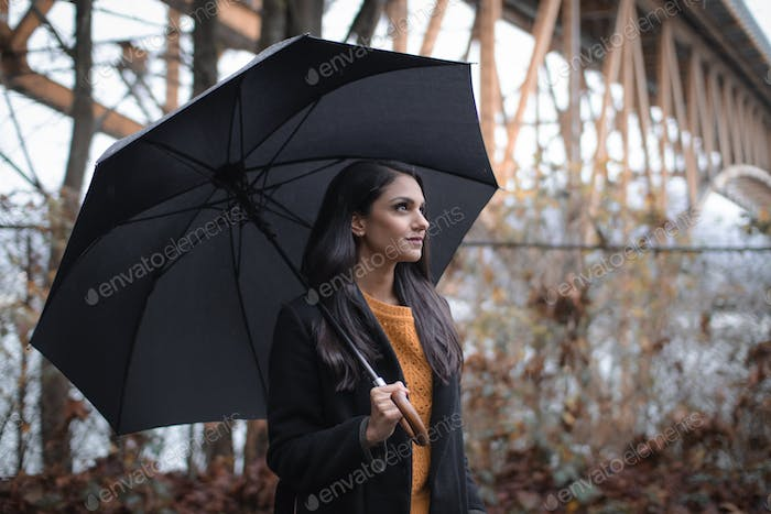 Beautiful young woman walking with an umbrella on a rainy day