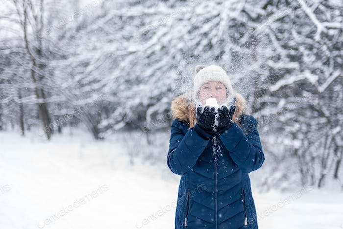 girl blowing a handful of snow in winter wonderland