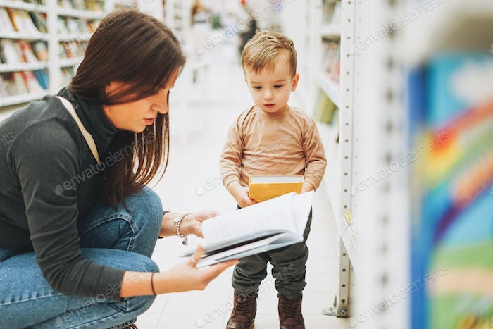 Cute baby boy toddler child in bookstore with mother with open book