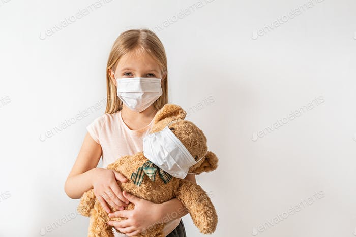 Little girl and teddy bear wearing protective face mask during coronavirus covid-19 pandemic