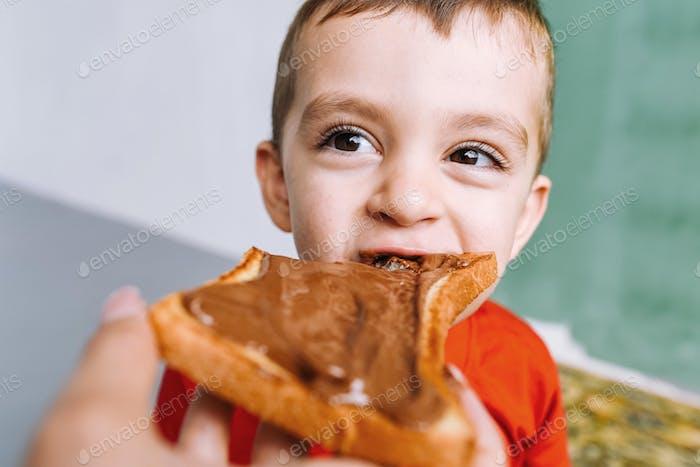 Ein Kind isst einen Toast mit Erdnussbutter aus den Händen seiner Mutter.