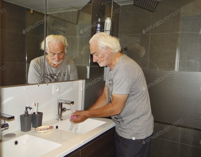 Elderly man washing his hands with soap in the bathroom