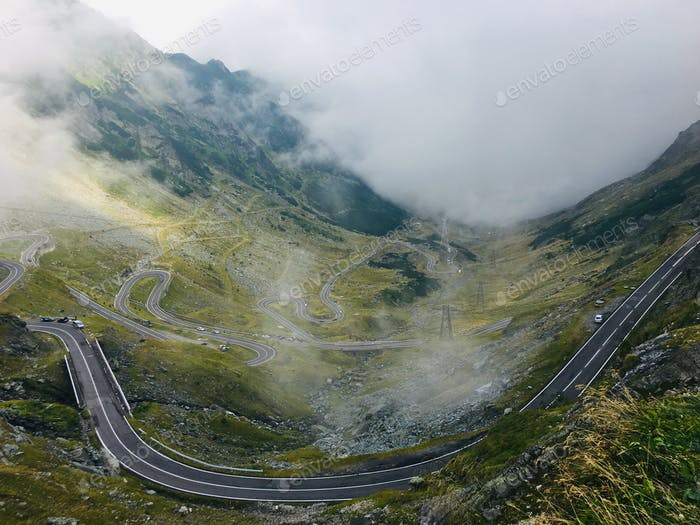 A very curvey road in the mountains during a Foggy day from panorama view