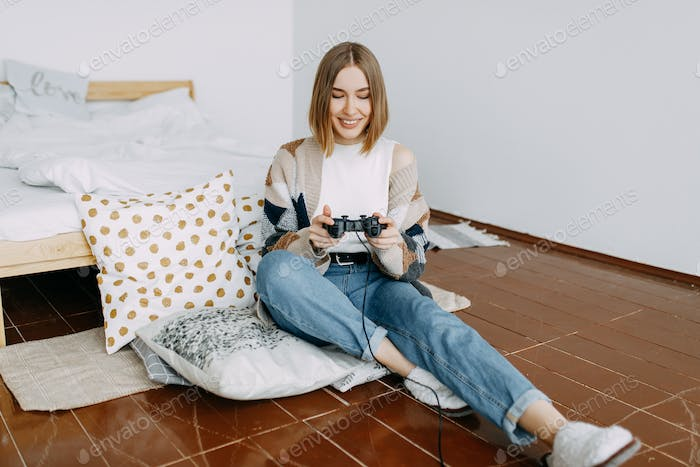a happy girl in casual clothes plays on a video console sitting on the floor in the bedroom at home