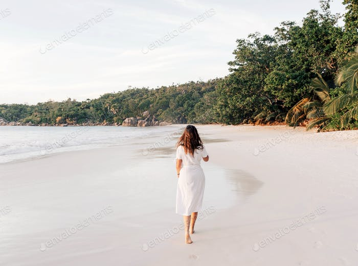 Young woman in white dress on sandy beach at sunset