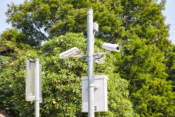 Security cameras or Surveillance CCTV outdoors in the public park with green tree background