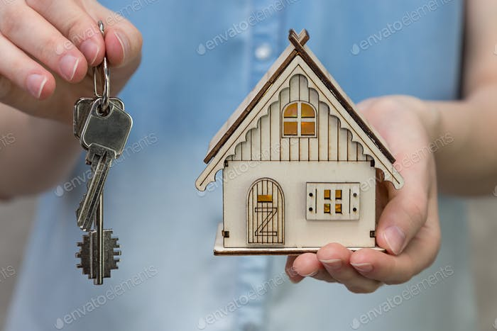 a toy house and a bunch of keys in female hands