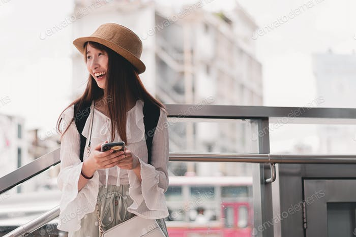A beautiful Asian traveler using smartphone in front of public transportation station.