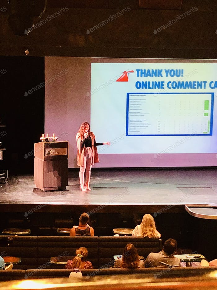 Confident woman on stage public speaking.