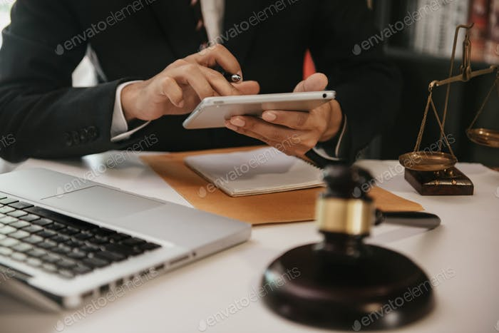 Lawyer business man working with tablet and paperwork on his desk in office workplace for consultant