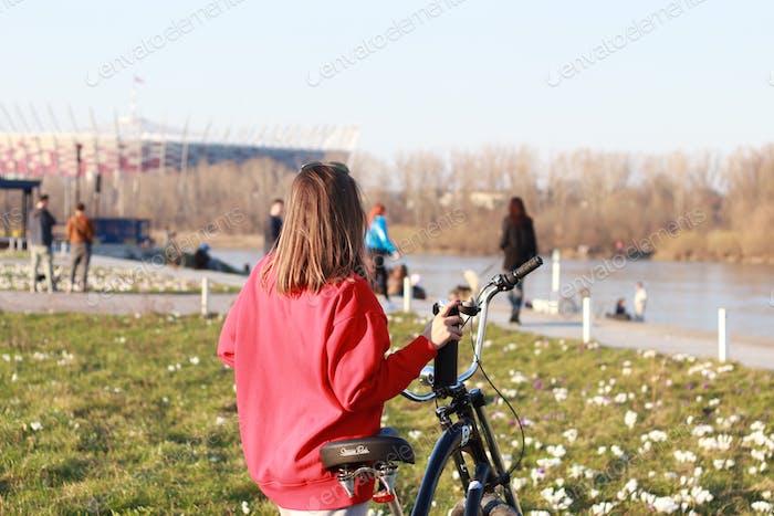 Una mujer con una sudadera roja se encuentra en la orilla del río, un descanso en el ciclismo.