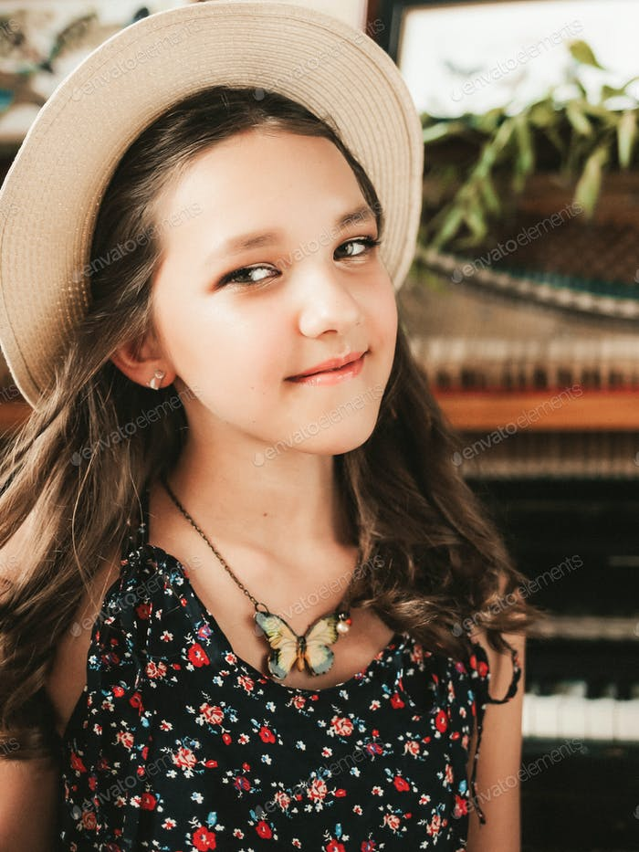 Portrait of a cute smiling teenage girl with curly hair in a sundress and hat