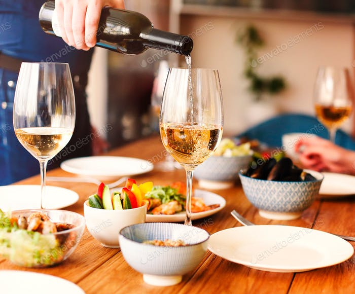 Crop anonymous male standing at table with various dishes and pouring wine into glass during home