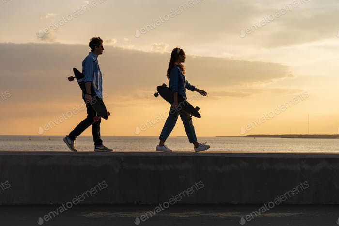 Couple of young longboarders walk on seaside carrying skate at sunset. Lifestyle and freedom concept