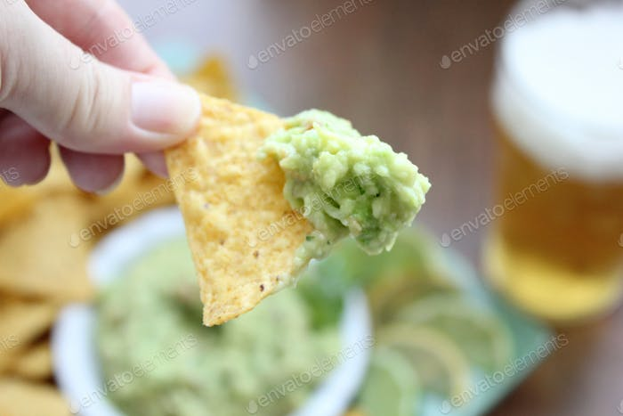 Guacamole dip on a corn chip for the Superbowl party food