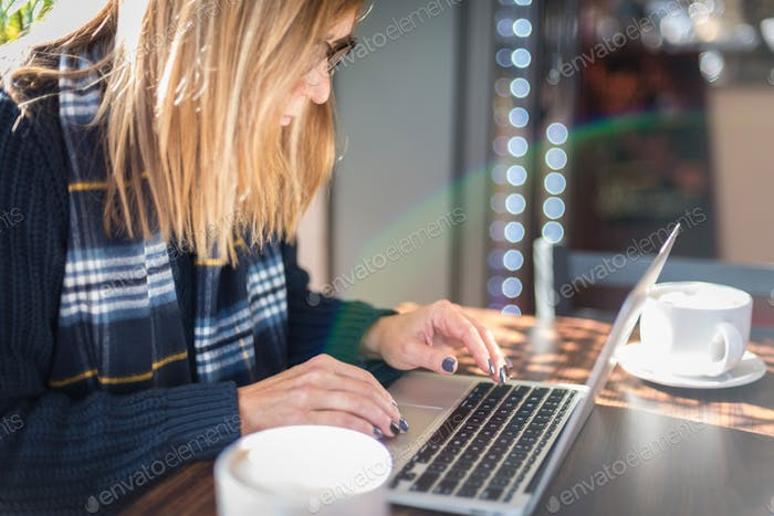 Woman in coffee shop using laptop with rainbow lens flare
