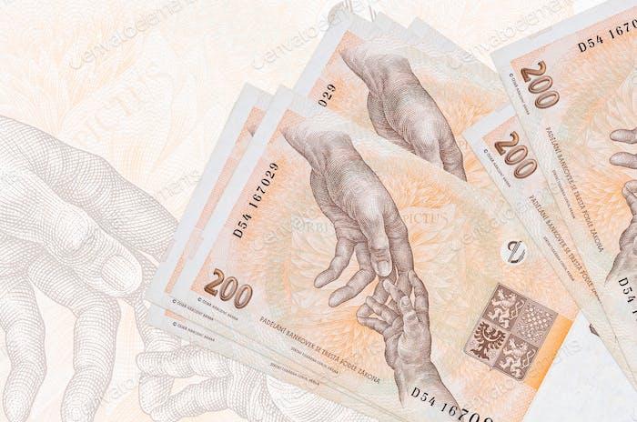 200 Czech korun bills lies in stack on background of big semi-transparent banknote. Abstract presen