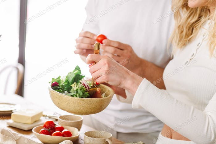 Young loving couple in white preparing healthy food together in the kitchen - fresh vegetable salad