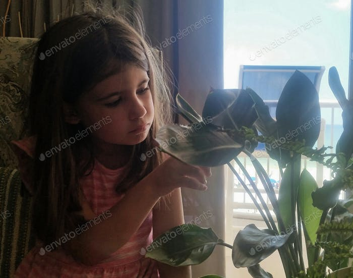 Little girl trying to figure out how to get a green finger...