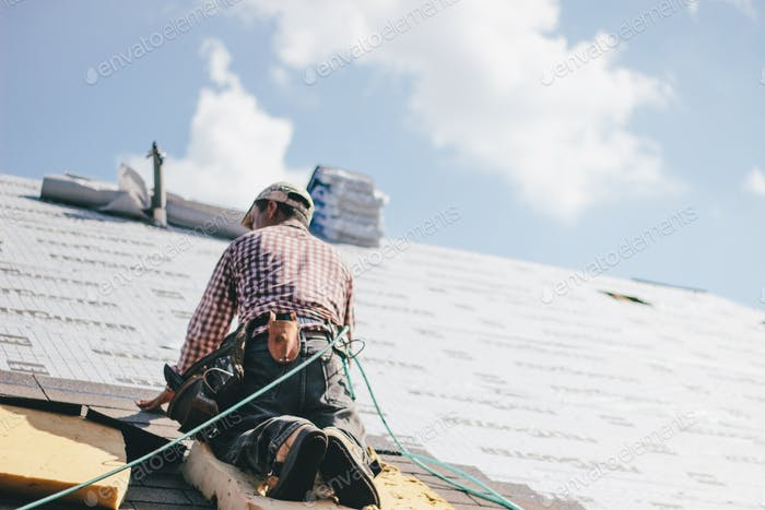 Roofer adding shingles to the roof of a house