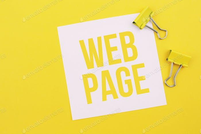 Clips de papel y en blanco con la inscripción de la página web sobre un fondo amarillo.